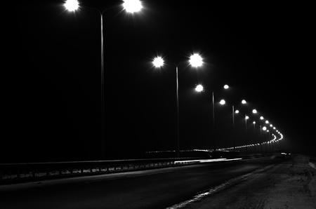 nighty: Black-and-white landscape of a night highway with a number of lampposts, fires of the cars, showing speed, time. Associations with despondency, depression, secret, progresstransportation, sports, progress, organized, exterior, nightlife, fuel, way, advent Stock Photo