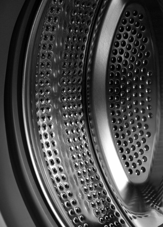 Black and white photo of a metal drum washing machine, which reflects the power, depth, an abstract force technology, work photo