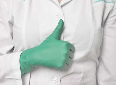 hand in glove, showing okay sign on the white background of medical coat photo