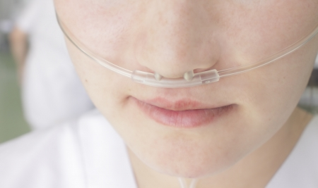 Breathing through a plastic nasal catheter during illness photo