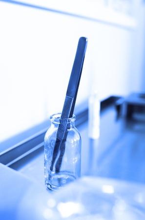 utiles de aseo personal: Pinzas en un frasco de vidrio en la mesa de ambulancia.