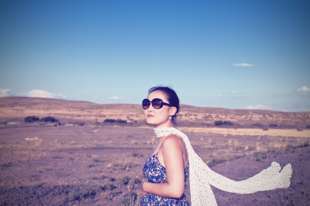 sundress: young pregnant Asian woman with a scarf to developing holding on to her belly on the background of desert nature