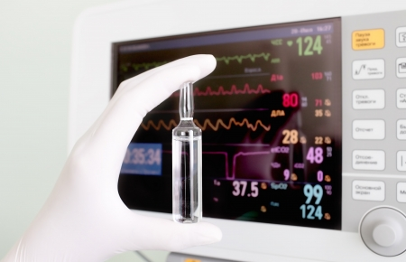 hand of doctor holding medicine against heart monitor  close-up photo