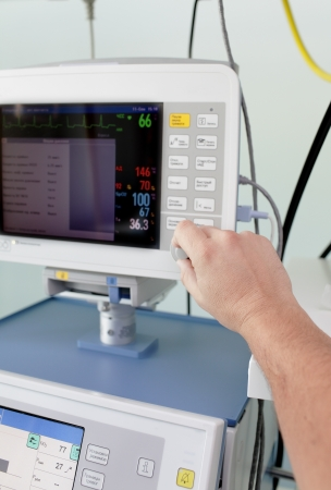 apparatus: regulation of medical monitor  Hand of doctor adjusts monitor in a hospital  Stock Photo