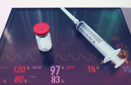 parameters: medicine and syringe on digital tablet with ECG and other patient parameters