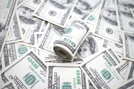 composite image: money concept  roll of dollars against many others  Stock Photo