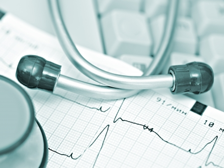 medical technical equipment: ECG and stethoscope against the keyboard