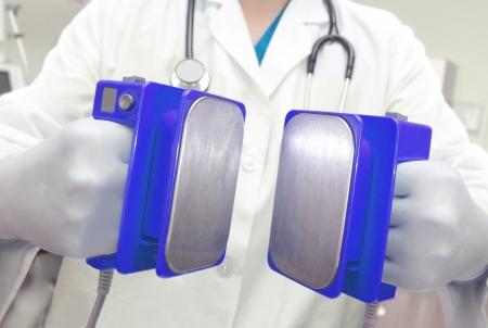 paramedic: Desfibrilador está listo para el doctor de descarga con electroshock en la mano