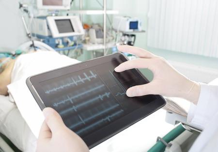 在現代醫院的醫生的先進技術觀看的平板電腦,患者心電圖