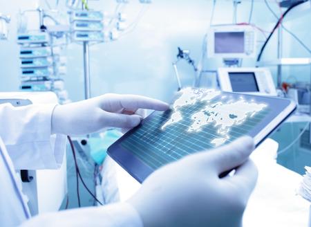 Medico che lavorava con tablet PC e mappa del mondo. Il concetto di Medicina