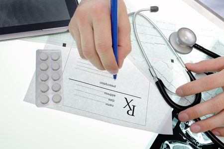 medical distribution: Doctor Having examined patient data, writes a prescription Stock Photo