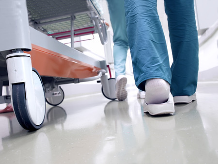 hospital stretcher: Medical staff moving patient through hospital corridor Stock Photo