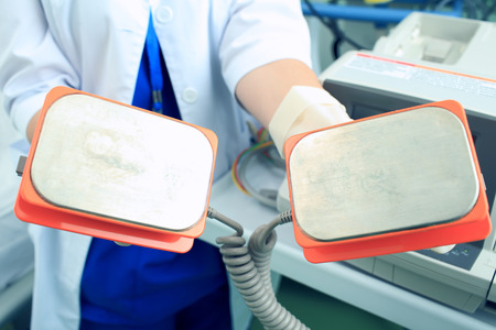 cardioverter: Plates defibrillator in the hands of the doctor is ready to save a life Stock Photo