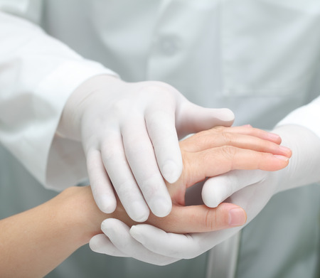 incurable: Doctor comforting a sick woman. Hands in warm touch. Stock Photo