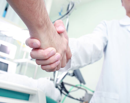 The doctor shakes hands with a patient in a medical room photo