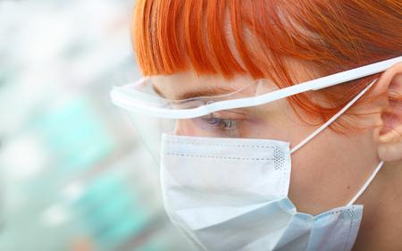 descubridor: Cient�fico de sexo femenino joven en gafas protectoras y mascarilla quir�rgica mira con atenci�n en el moderno laboratorio