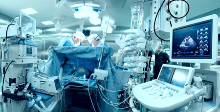 In advanced operating room with lots of equipment, patient and working surgical specialists 免版税图像