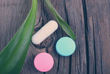 vitamin pill: Capsules, tablet and plant on a wooden background