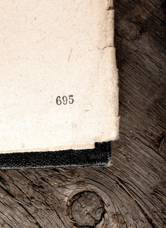Old shabby book apened on obsolete wood background photo