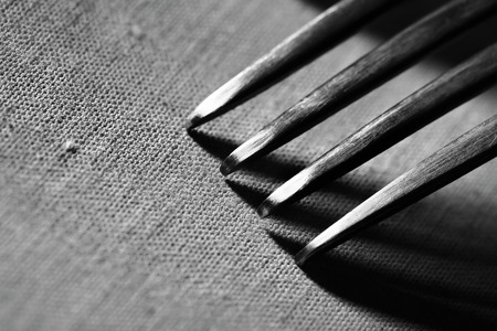 macros: Fork on rough fabric textured background macro