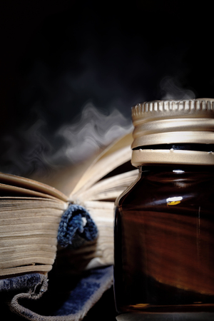 libros antiguos: Abra el libro de humos y la botella con la poción mágica Foto de archivo