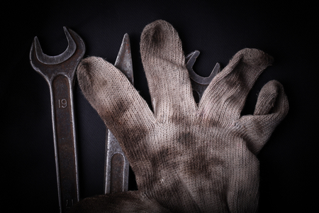 manual work: Wrenches and dirty glove on a black background concept of manual work