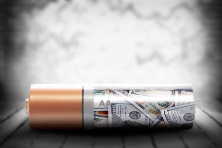 deposit: Alkaline battery with dollars inside on grunge background Stock Photo