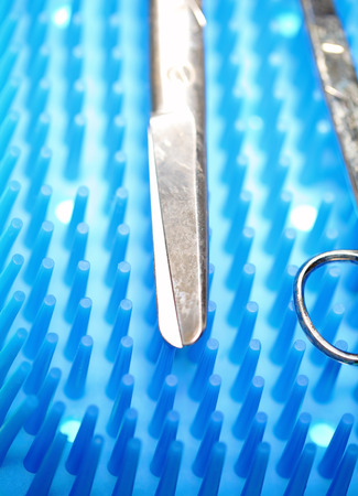 operating table: Scissors on the operating table with tools in hospital Stock Photo
