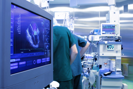 healthcare professional: Ultrasound monitor in the operating room at the background of the doctors, the concept of teamwork Stock Photo