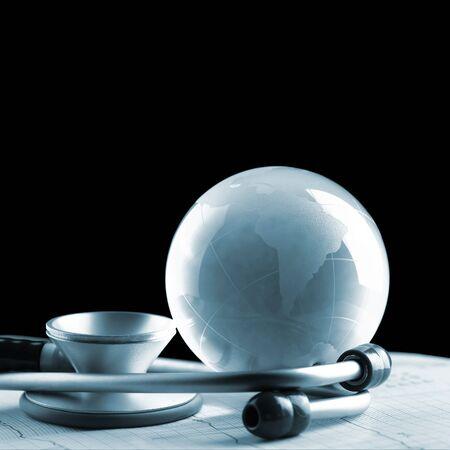 natural phenomena: Glass globe and stethoscope isolated on a black background