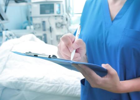 Mujer médico monitoriza la condición del paciente y llena documentos