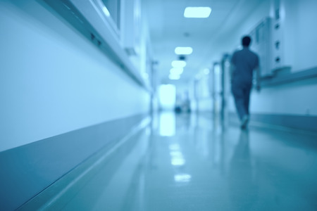 Blurred medical background. Moving human figure in the hospital corridor Фото со стока