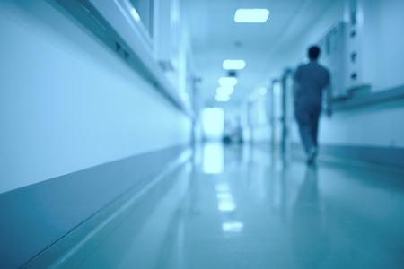 egészségügyi: Homályos orvosi háttér. Mozgó emberi figura a kórházi folyosón