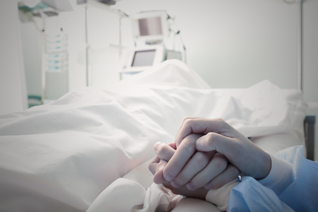torment: Holding the hand of a dying man in hospital
