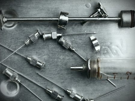 parenteral: Obsolete glass syringe and needles in the steel tray Stock Photo