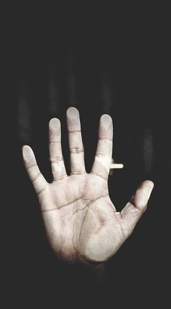 torment: Mens palm pressed to the glass on the black background, the metaphor of despair Stock Photo