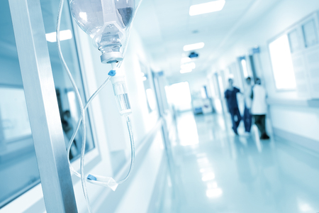 Drip on the background of talking doctors in hospital corridor