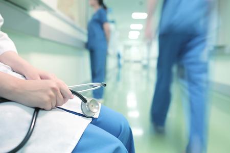 Arts zittend alleen in ziekenhuis gang op de achtergrond van lopende collega's