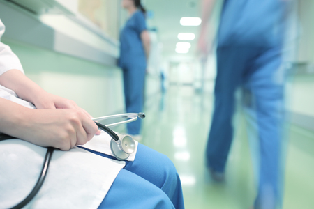 Doctor sitting alone in hospital corridor on the background of walking colleagues Archivio Fotografico
