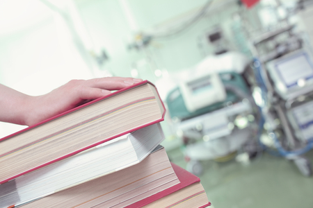 Stack of books in hospital ward, concept of professional development.
