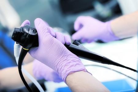 guantes: Instrumento de la endoscopia en las manos del doctor. Foto de archivo