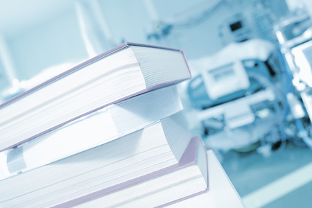Pile of books on a background of hospital patient beds