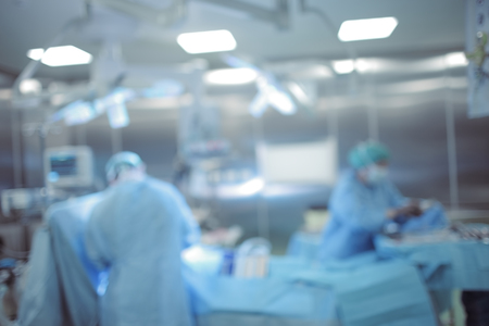 Operates team of surgeons at the hospital, blurred background.