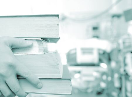 trainee: Stack of books in hands of young trainee doctor.