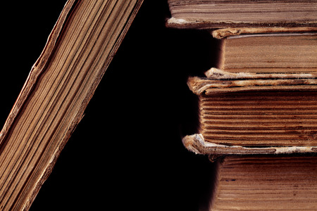 stacked books: Old books on black background.