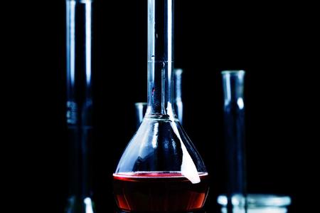 retort: Red liquid in chemical beaker.