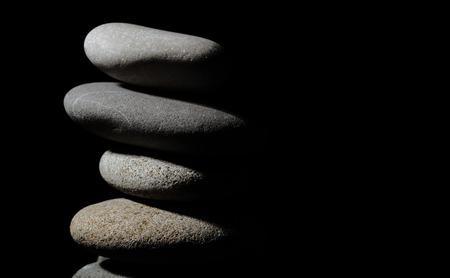 black stones: Pile of grey stones on the black background Stock Photo