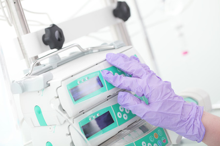 Medical workers hand in protective glove in intensive care unit.