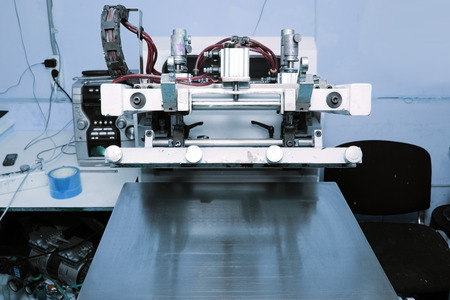 Screen printing machine in the printing workshop. Foto de archivo