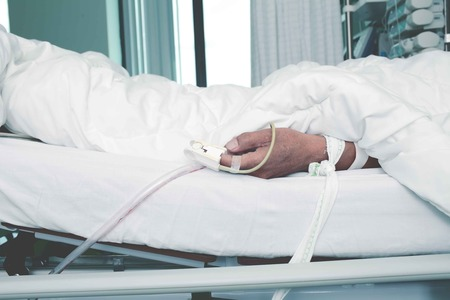 critical care: Patient tied to a bed in the critical care unit.